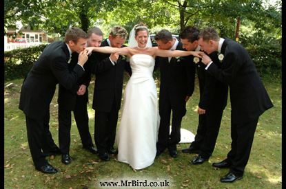Bride being kissed on the hand and arms by the groom, best man and ushers, she has a big smile!