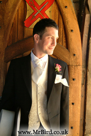 Top hat and tails, groom waits at the church door for his bride