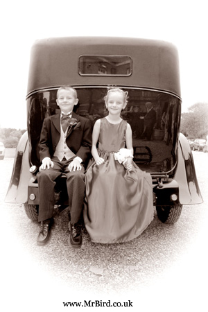 Page boy and brides maid sitting on the bak of the wedding car