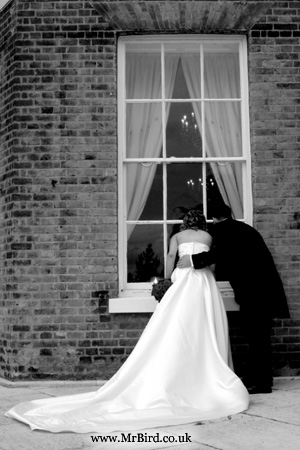 cheeky bride and groom looking through the window of their wedding reception