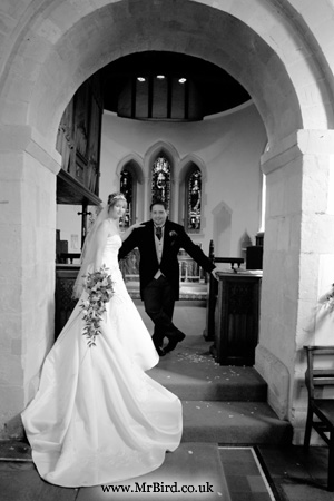 bride with a long wedding dress train and groom standing in the churh archway