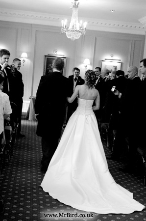 bride being walked down the isle by her father and the groom smiling at her ibn black and white